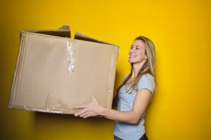 Blond lady holding a box in front of a yellow wall
