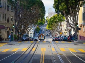 Street with trees, cable car and buildings.