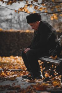 Elderly man sitting on a bench in a park thinking about unpacking after senior relocation