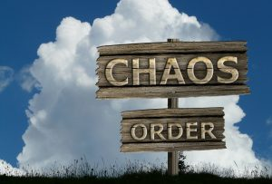 A wooden sign with the words ''chaos'' and ''order''