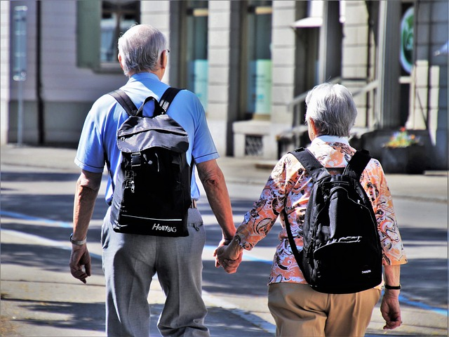 An elderly couple walking down the street hand in hand and talking about retiring in LA.