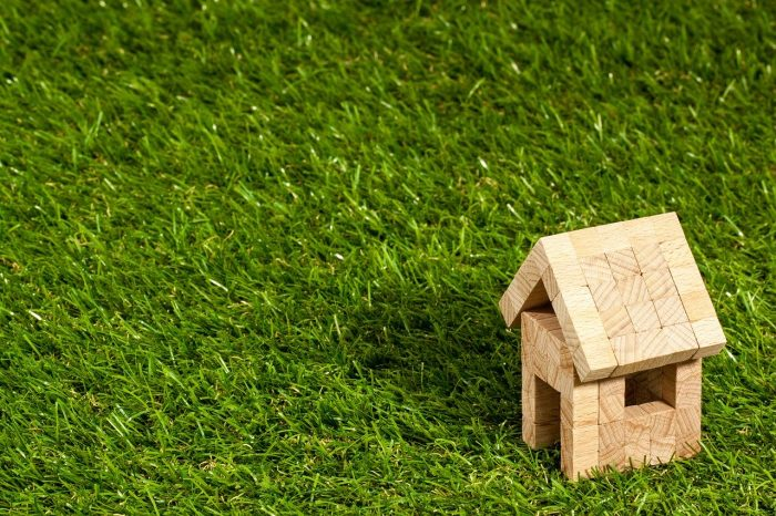 A small house made out of wooden block sitting in a field of grass.