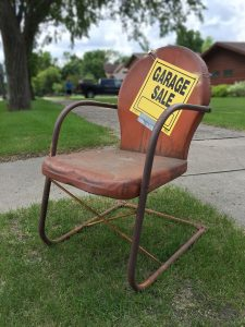 "An old chair with a sign that says ""Garage sale""."