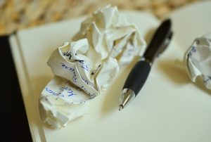 Scrunched up piece of paper and a pen next to it to illustrate that it is not easy to keep track of your money when moving