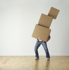 A man barely managing to hold a few moving boxes.