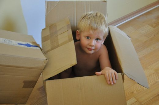 A boy playing in the box because the kids always have an idea about how to utilize wardrobe boxes after relocation.