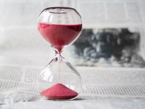 A hourglass with pink sand in it.