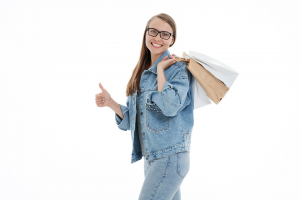 A girl wearing denim and holding bags over her shoulder gives a thumbs up.