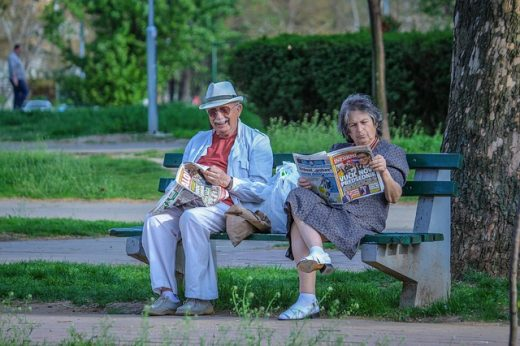 An elderly couple sitting on a bench and discussing the relocation guide for seniors