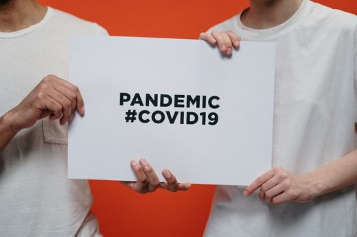 Two people holding a piece of paper which says pandemic COVID-19.