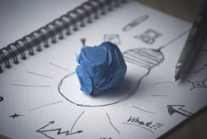 A piece of blue crumpled papaer on a drawn light bulb.