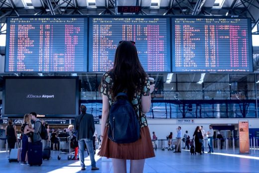 A young girl at an airport looking at the departures board before moving internationally