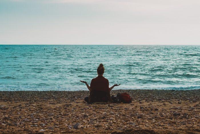 A girl meditating on the beach.