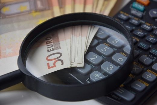 A magnifying glass, money and a calculator to symbolize Calculating the costs of moving to another continent,
