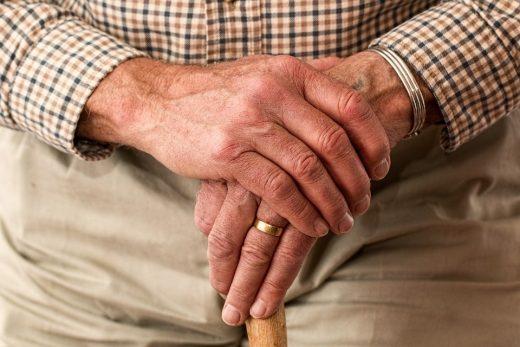The hands of an emderly man holding a walking stick.