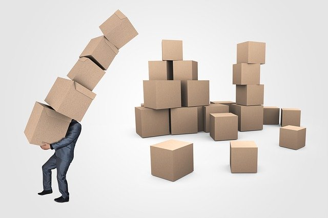 A man carrying the boxes and wondering about the creative ways to use leftover moving boxes.