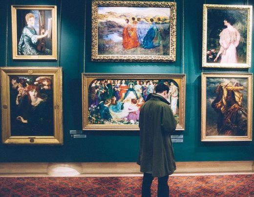 A man looking at paintings.
