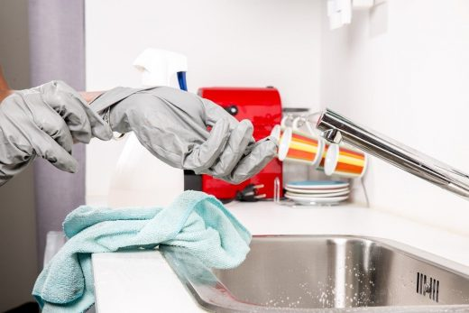 A woman washing the dishes with rubber gloves.