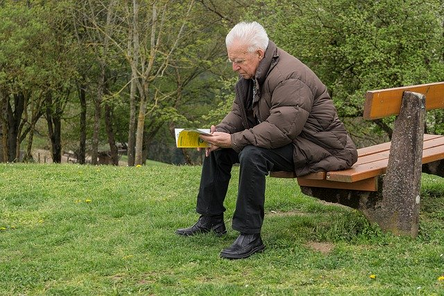 An elderly man sitting on a bench in a park and reading about the best cities in Maryland to retire