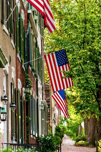 A peaceful neighborhoods with American flags hung on homes.