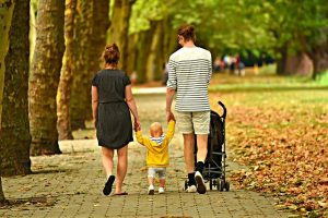 Parents walking their child in the park and discussing living in Plymouth Meeting.