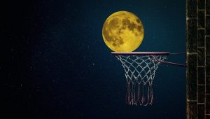 A photo of the moon as if it is was a baskteball scoring a point as sports are one of the ways to deal with homesickness.