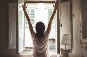 A woman stretching next to an open window.