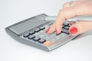 A hand typing on a calculator while trying to set the costs, so you can organize your Ottawa-based company.