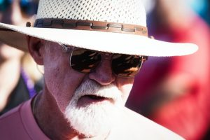 An elderly man with a hat and sunglasses.