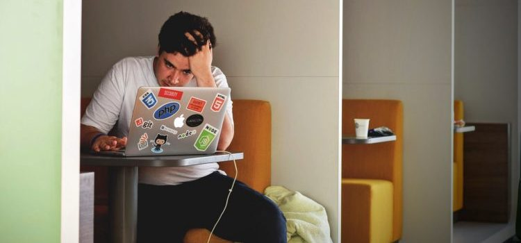 A stressed out person looking into his laptop