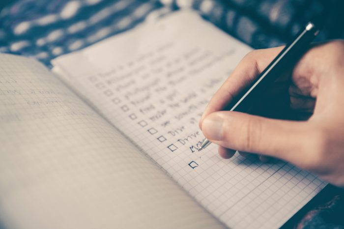A person creating a checklist before buying a home in Charlotte.