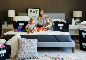 kids and mom sitting on the bed packing