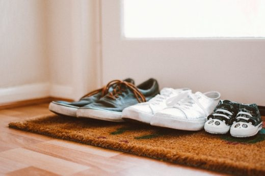 There are three pairs of shoes on a doormat.